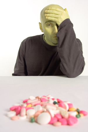 A sick man, looking very green from a bad hangover, wearily looks through a fog at a pile of drugs and medication, hoping some of them will make him feel better. Stock Photo - 1498121