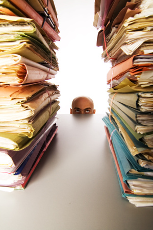 arquivos: Man with bald head peaks above desk to see stacks of files and folders waiting for his attention.
