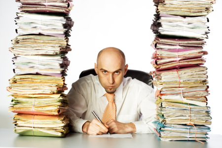 clearly: A stern and unpleasant administrative clerk glares through two huge stacks of business files, clearly indicating he has not time or desire to be of any customer service.