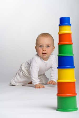 dazzled: Bright-eyed baby crawling toward a colorful stack of containers.  Stock Photo