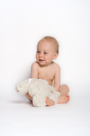 Cute baby boy sits on the floor with his favorite stuffed animal, a white teddy bear.  photo