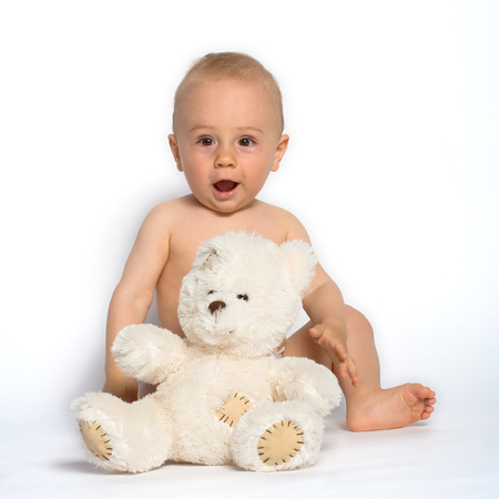 Cute baby boy sits on the floor with his favorite stuffed animal, a white teddy bear.