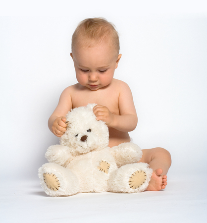 Cute little baby boy with mischievous grin plays quietly with a white teddy bear.