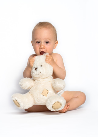 contentment: Cute little boy holding a white, stuffed teddy bear. White background.