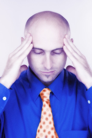 Man with tips of his fingers pressed against his temples, looking down, looking stressed and trying to relax. Stock Photo - 1677680