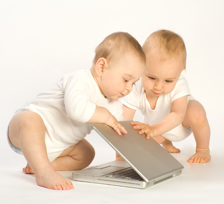 Two toddling boys trying to open laptop