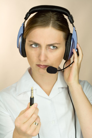 unplugged: Woman with headset and microphone discovering she´s unplugged Stock Photo