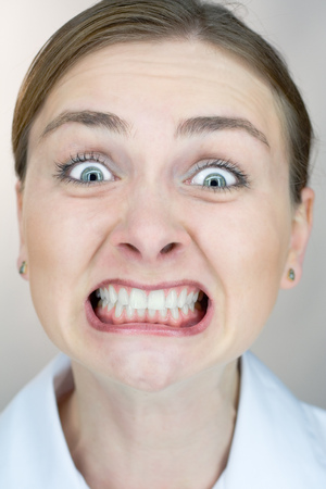 overwrought: Closeup of a womans face with uptight expression.