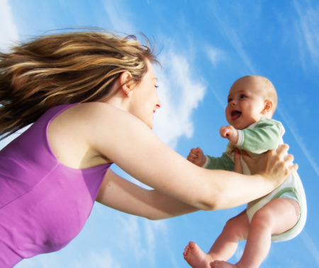 A young woman with flowing blond hair, holds a smiling, happy baby in diapers up over her head against a bright blue sky.