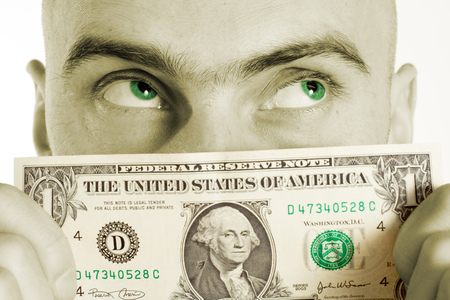 A man holds a US one dollar bill to his face obsesessed with a fantasy of more money. The color of his eyes has been changed to match the green color in the dollar bill.