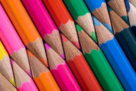 interlocked: Tips of sharpened colored pencils, artistically arranged with points closely aligned in an interlocking, diagonal display of color.  Stock Photo