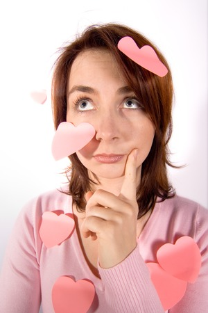 A pretty young girl with a puzzled and bewildered look and wearing a pink top, has a number of pink valentine hearts stuck to her as reminders that Valentines Day is coming.