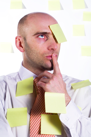 worrying: Unorganized businessman desperately uses post-it notes to somehow remember important details and schedules.