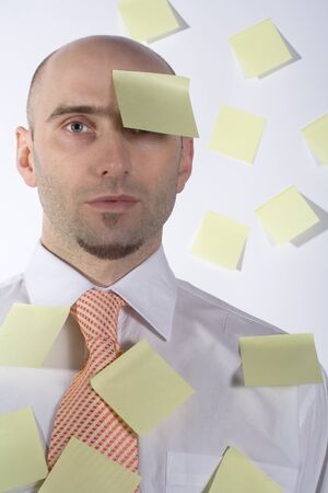 uptight: Unorganized businessman desperately uses post-it notes to somehow remember important details and schedules.