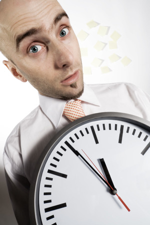 A busy businessman holds a huge analog clock indicating that time and scheduling is a very important consideration for him.  Stock Photo