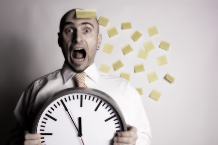 Frantic, unorganized businessman unsuccessfully tries to use many post-it notes to remind him of his busy schedule and appointments.  Stock Photo