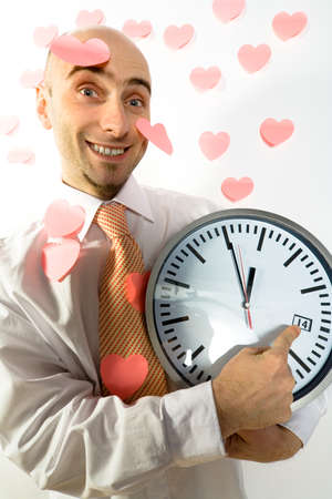 rushing hour: A man pointing to a clock signaling Valentines Day. Stock Photo