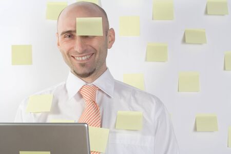 unsuccessfully: Unorganized businessman uses post-it notes to keep from forgetting important details and appointments.