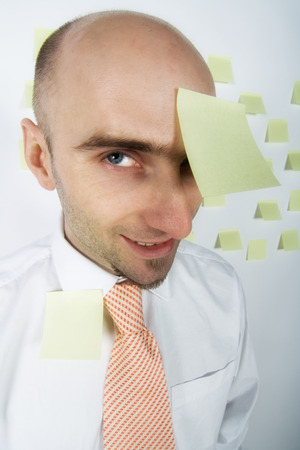 An inept businessman with a very poor filing and appointment system, using multiple post-it notes to remind him of important dates, appointments, and deadlines, including one stuck to his forehead! Stock Photo