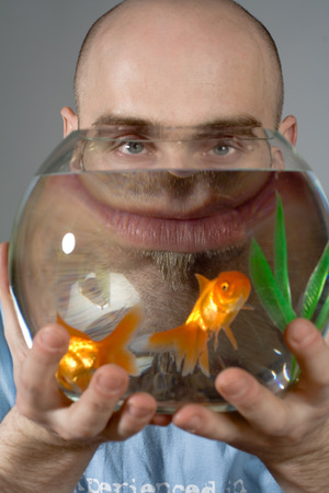 A man holds a glass goldfish bowl with two goldfish swimming in it.  Unusual optical illusions appear in the bowl.