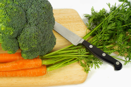 brocolli: A bundle of both carrots and Brocolli on a cutting board with a knife.