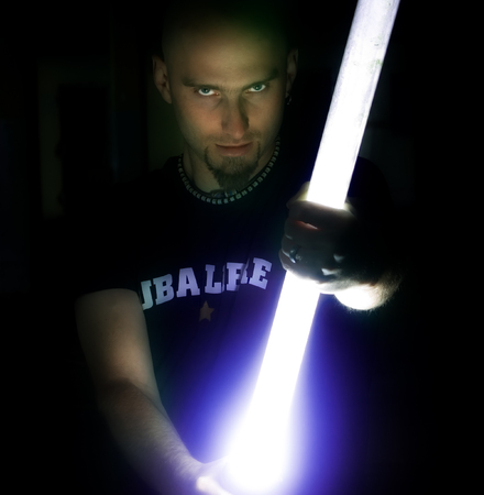 A man holds a long, glowing Star Wars light stick in his hands in the dark.