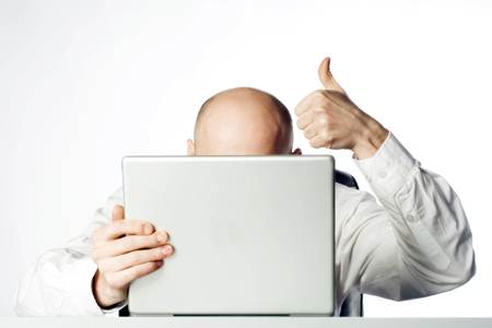 Bald businessman giving the thumbs up signal while hunkering behind laptop computer.  White Background.