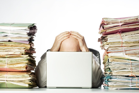 Male businessman sitting behind a laptop, his face hidden, with his hands on top of his head.  Two large piles of paperwork are piled on each side of the model, towering over his head.  Isolated on white background.