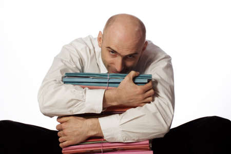 clutching: Baldheaded office worker sitting and clutching piles of files