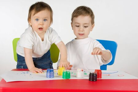 litlle boy and girl enjoy painting with assorted colours photo