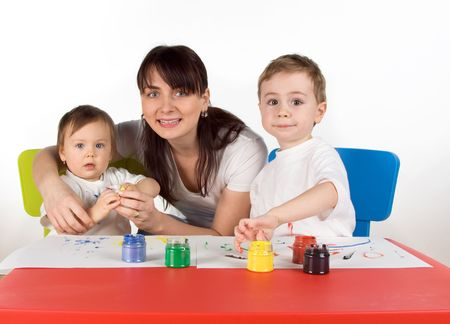 childern: Mother with her childern enjoy painting with assorted colours