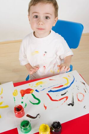 little boy paint with own hand and use assorted colours photo