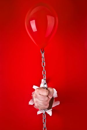 Close up of human hand protruding through hole in red background, holding red balloon on chain. photo
