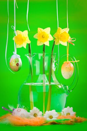 Yellow narcissus in glass flagon with decorated eggs, flowers and colored feathers on green background photo