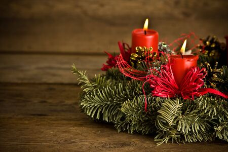 Green christmas wreath decorated with red burning candles, red ribbons and golden pine cones on timber floor photo