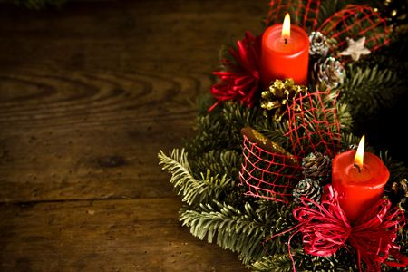 Green christmas wreath decorated with red burning candles, red ribbons and golden pine cones on timber floor Standard-Bild