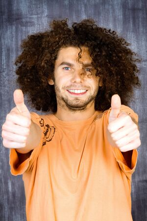 Handsome smiling young man with long afro hairstyle and two thumbs up. photo