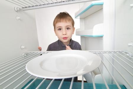 Boy looking into empty refrigerator. photo