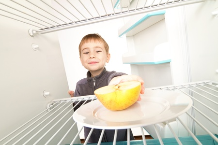 frig: Boy looking into empty refrigerator seeing apple. Stock Photo