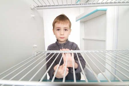 Boy looking into empty refrigerator. Stock Photo