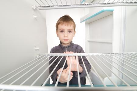 frigo: Gar�on regardant dans le r�frig�rateur vide.