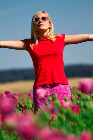 upraised: Teenage girl standing outdoors in a field of flowers with her arms outstretched and closed eyes.