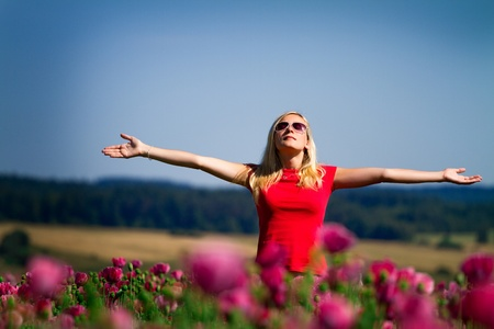 Teenage girl standing outdoors in a field of flowers with her arms outstretched and closed eyes.