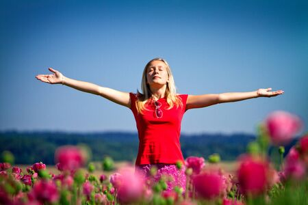 eye  closed: Teenage girl standing outdoors in a field of flowers with her arms outstretched and closed eyes.