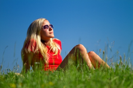 leans on hand: Attractive blond haired teenager with sunglasses relaxing on green countryside meadow with blue sky background.