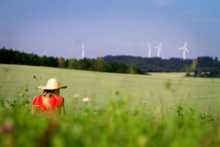 long weekend: A girl sitting in a field in summer wearing a straw sun hat and red t.shirt.  Stock Photo