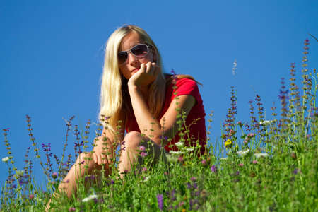 Attractive blond haired teenager with sunglasses relaxing on green countryside meadow with blue sky background. photo