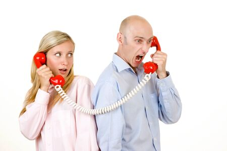 Upset man yelling at a frightened young woman on a red telephone. Stock Photo - 9526314