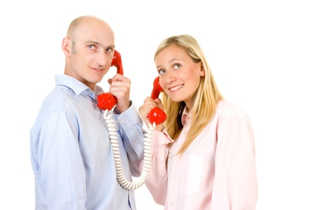 Happy young couple connected with red retro style telephones; white studio background. Stock Photo - 9526503