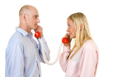 Man and woman holding red telephone receivers that are connected.  Isolated against a white background. Stock Photo - 9526506